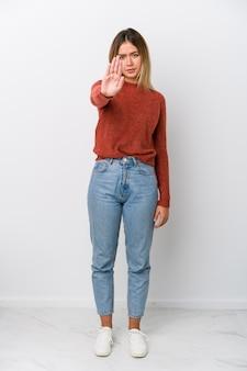 Całego ciała młoda caucasian kobieta stoi z wyciągniętą ręką pokazując znak stop, zapobiegając ci.