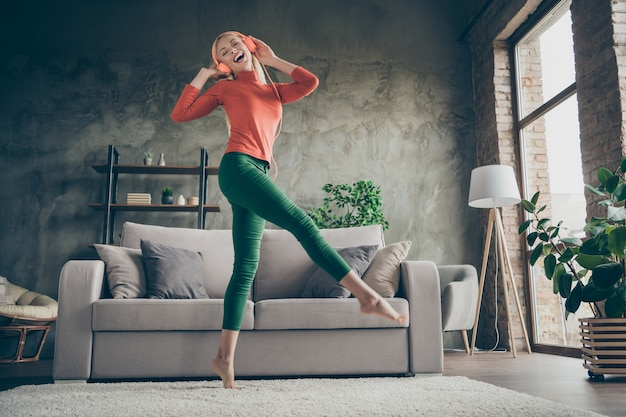 Całego ciała z niskiego kąta widzenia zdjęcie całkiem zabawnej pani trzymającej telefon słuchającej piosenki nowoczesne pomarańczowe słuchawki tańczące w pobliżu kanapy strój codzienny salon w pomieszczeniu