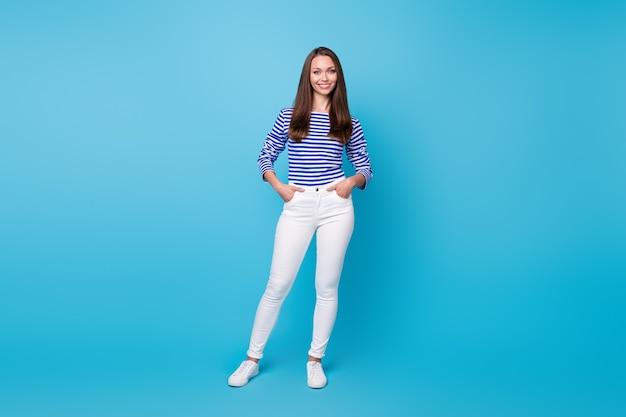 Całego ciała zdjęcie wielkości całkiem młoda dziewczyna szczupła sylwetka ręce kieszenie kobieta koncepcja wakacje nosić koszula w paski białe spodnie trampki na białym tle żywy niebieski kolor tła