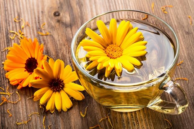 Calendula ziołowa herbata w przejrzystym szklanym kubku z wysuszonymi kwiatami na drewnianym wiejskim tle.