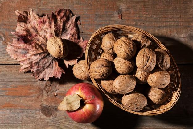 Cali orzechy włoscy z jabłkiem na nieociosanym starym drewnianym stole. zdrowa żywność, zdrowy tłuszcz, najdalszy upadek.