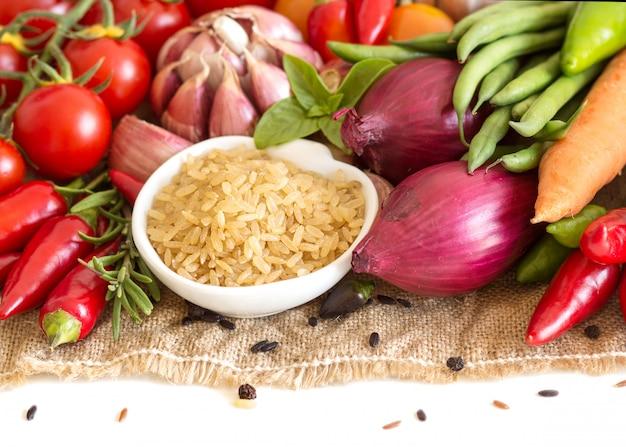 Cali upolished organicznie ryż w pucharze z surowymi warzywami zamykają w górę odosobnionego na bielu z kopii przestrzenią