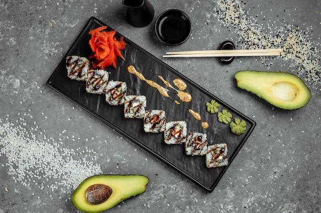 California roll sushi z wędzonym węgorzem, ogórkiem, awokado. menu sushi. japońskie jedzenie.