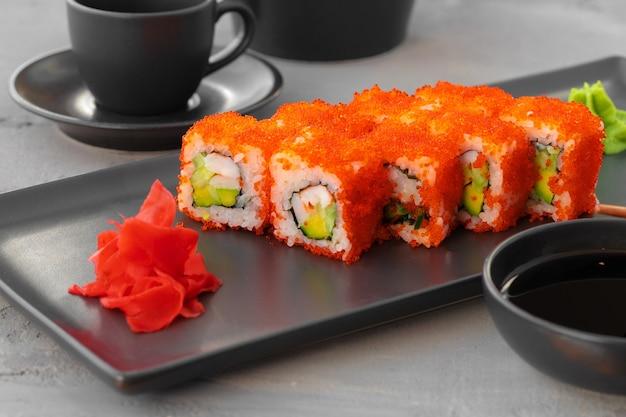 California sushi roll podana na czarnym talerzu ceramicznym