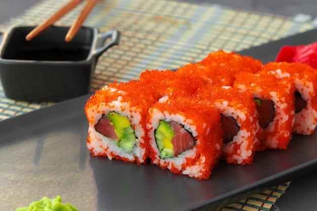 California sushi roll serwowane na czarnej płycie ceramicznej z bliska