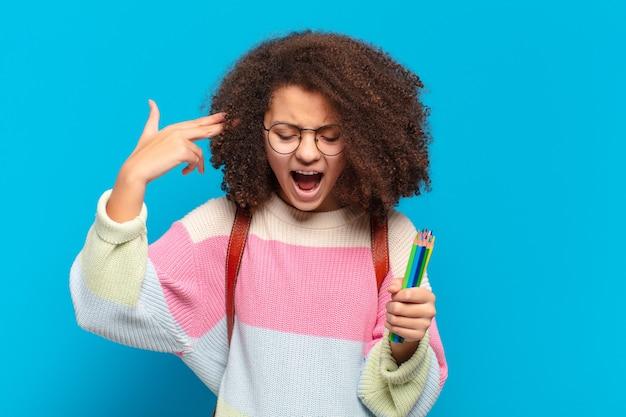 Całkiem afro nastolatek wyglądający niezadowolony i zestresowany, samobójczy gest czyniąc znak pistoletu ręką, wskazując na głowę. koncepcja studenta