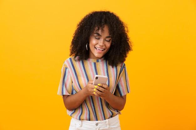 Całkiem afrykańska kobieta pozowanie na białym tle nad żółtą przestrzenią za pomocą telefonu komórkowego.
