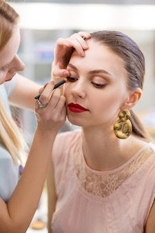 Całkiem atrakcyjna kobieta, która ma nałożony makijaż podczas wizyty w studio urody