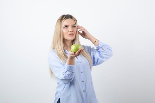 Całkiem atrakcyjna modelka kobieta stojąca i trzymając zielone świeże jabłko.