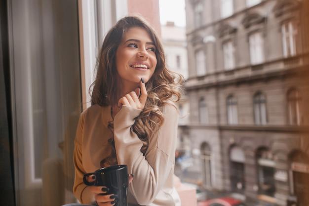 Całkiem biała kobieta figlarnie dotykając palcem brody, patrząc na miasto