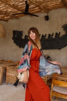 Całkiem biała kobieta w stylowym letnim bohemain autfit pozowanie w tropikalnej kawiarni.