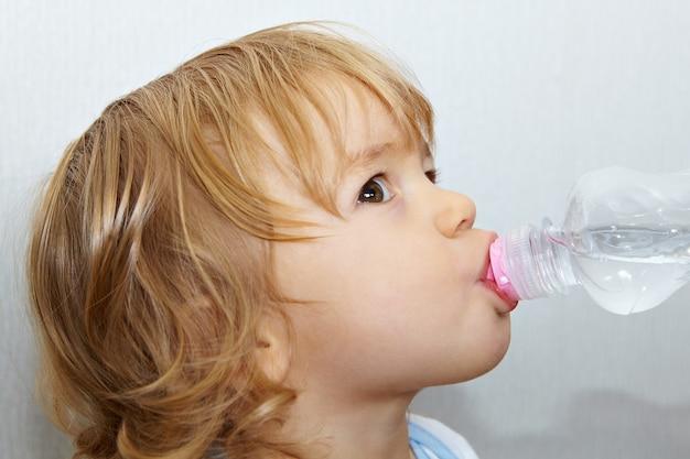 Całkiem białe kaukaskie małe dziecko z blond kręconymi włosami i brązowymi oczami pije wodę z butelki.