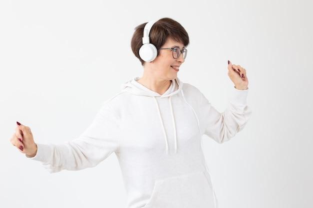Całkiem bystra kobieta w średnim wieku w okularach i białym swetrze słucha swojej ulubionej muzyki w słuchawkach na białej ścianie