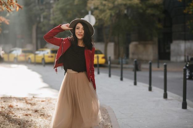 Całkiem ciemnowłosa kobieta w stylowej długiej spódnicy chłodzenie w parku