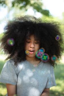 Całkiem czarna nastolatka bawiąca się bańkami mydlanymi