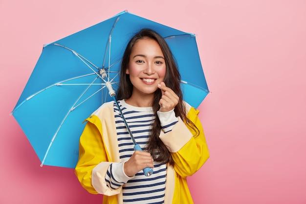 Całkiem czuła azjatka robi koreański znak jak znak, ma szczęśliwy wyraz twarzy, delikatny uśmiech, stoi pod parasolem, nosi żółty płaszcz przeciwdeszczowy