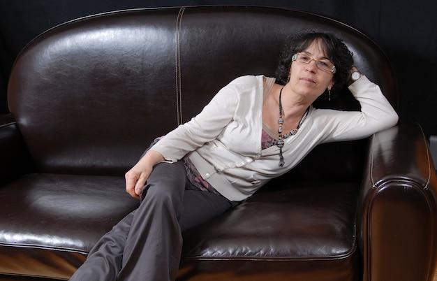 Całkiem dojrzała kobieta siedzi na kanapie