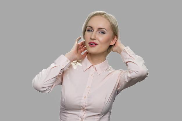 Całkiem elegancka kobieta flirtuje. atrakcyjna blondynka w średnim wieku ubrana w koszulę biurową flirtuje do kamery na szarym tle.