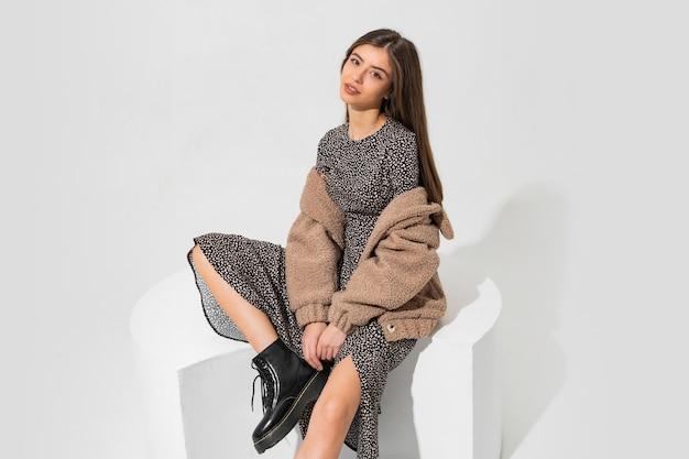 Całkiem europejskiej kobiety w zimowe futro i stylowa sukienka siedzi. nosi botki z czarnej skóry.