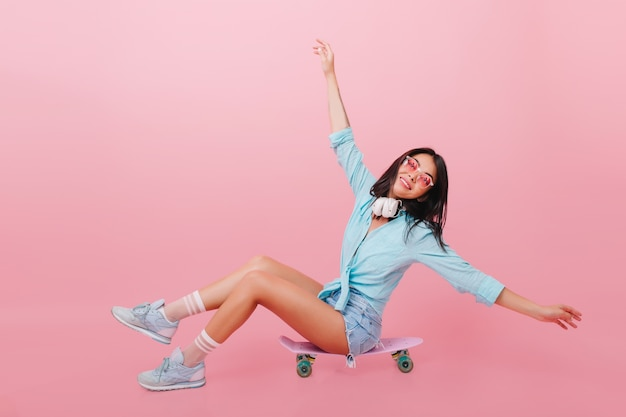 Całkiem hiszpanin kobieta z brązową skórą macha rękami siedząc na longboard. zainspirowana latynoska dziewczyna w okularach przeciwsłonecznych pozująca na deskorolce