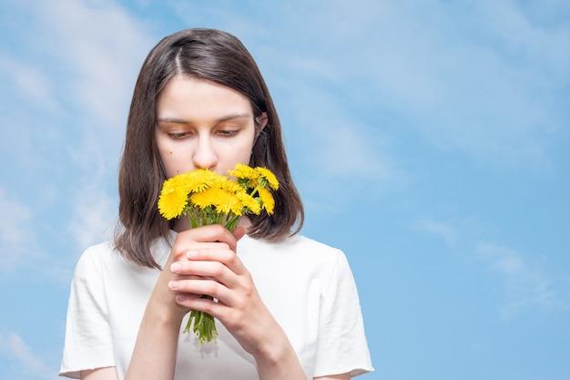 Całkiem kaukaska dziewczyna wdycha zapach żółtych mleczy na tle błękitnego nieba z chmurami, kopia przestrzeń. dziewczyna otrzymała w prezencie bukiet polnych kwiatów. letnie kwiaty w prezencie.