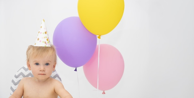 Całkiem kaukaski blond dziewczynka przy wysokim krześle przez kolorowe balony, w kapeluszu urodzinowym, patrząc na kamery. kartkę z życzeniami, makiety. impreza dla dzieci, pomysł na wakacje, świętuje dziecko. skopiuj miejsce na tekst.