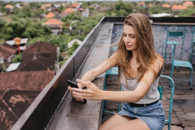 Całkiem kaukaski dziewczyna w dżinsowej spódnicy siedzi na dachu ze smartfonem. zewnątrz portret brunetki pani chłodzi na ulicy.