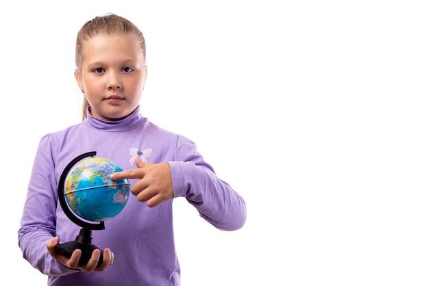 Całkiem kaukaski dziewczynka w fioletowym t-shirt trzyma kulę ziemską na białym tle.