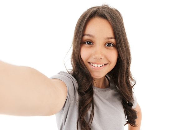 Całkiem ładna dziewczyna zrobić selfie patrząc aparatu.