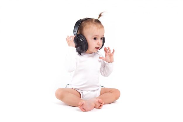 Całkiem ładna dziewczynka w białych pijamas ze słuchawkami na głowie