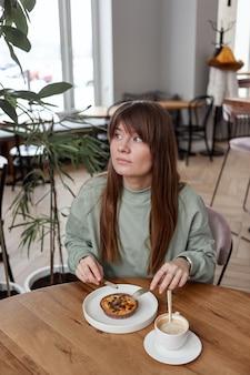 Całkiem ładna kobieta siedzi w pustej kawiarni zjada ciasto i pije kawę