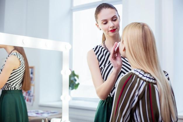 Całkiem ładna kobieta stojąca obok klienta i oczyszczająca skórę wacikiem
