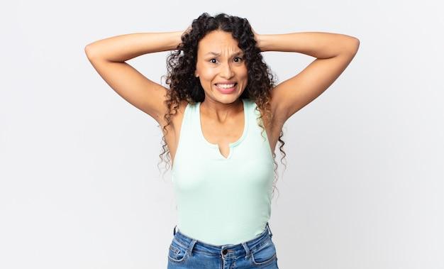 Całkiem latynoska kobieta czuje się zestresowana, zmartwiona, niespokojna lub przestraszona, z rękami na głowie, panikując z powodu błędu