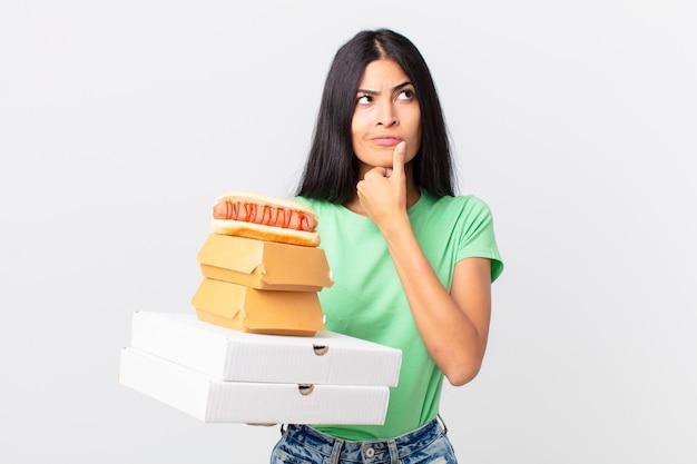 Całkiem latynoska kobieta myśli, czuje się zwątpienie i zdezorientowana i trzyma na wynos pudełka z fast foodami