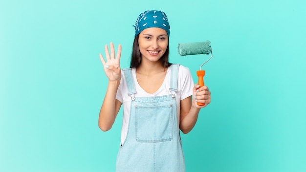 Całkiem latynoska kobieta uśmiechnięta i patrząca przyjaźnie, pokazująca numer cztery. koncepcja malowania domu