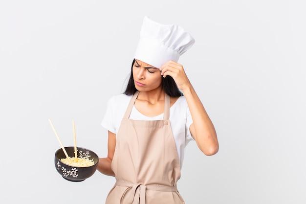 Całkiem latynoska szefowa kuchni czuje się zdezorientowana i zdezorientowana, drapiąc się po głowie i trzymając miskę z makaronem