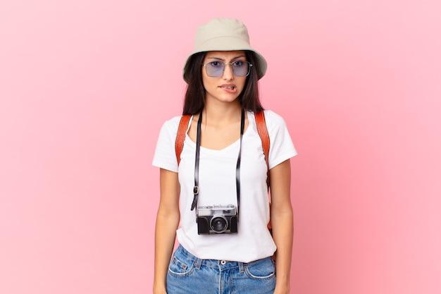 Całkiem latynoski turysta, który wygląda na zdziwionego i zdezorientowanego z aparatem fotograficznym i kapeluszem