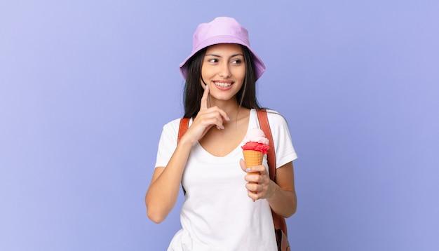 Całkiem latynoski turysta uśmiechający się radośnie i marzący na jawie lub wątpiący i trzymający lody