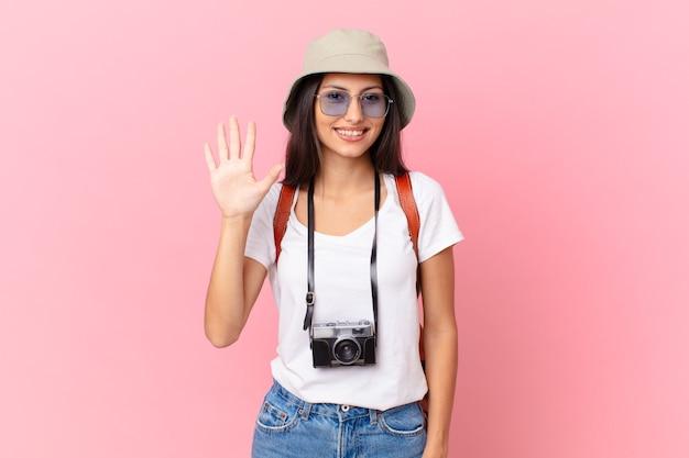 Całkiem latynoski turysta uśmiechnięty i wyglądający przyjaźnie, pokazujący numer pięć z aparatem fotograficznym i kapeluszem