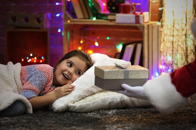 Całkiem mała dziewczynka leżąca na poduszce pod miękką kratą, czekająca na prezent od mikołaja w świątecznym pokoju
