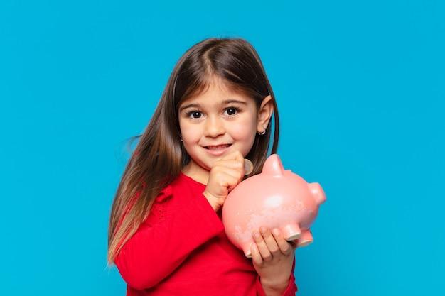 Całkiem mała dziewczynka myśli wyrazem twarzy i trzyma skarbonkę