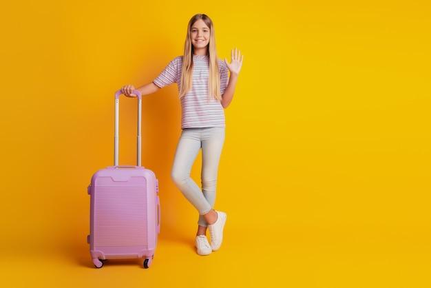 Całkiem mała dziewczynka na białym tle na żółtym tle trzyma rękę fala walizki