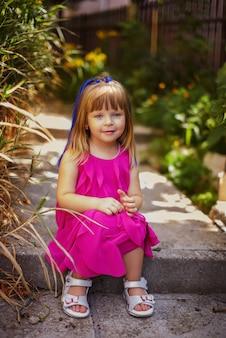 Całkiem mała dziewczynka na sobie sukienkę na zewnątrz w lecie