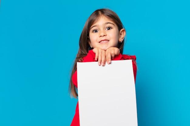 Całkiem mała dziewczynka przestraszona wyrazem kartki papieru
