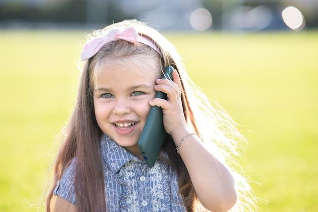 Całkiem mała dziewczynka rozmawia przez telefon komórkowy szczęśliwie uśmiecha się na zewnątrz w lecie.