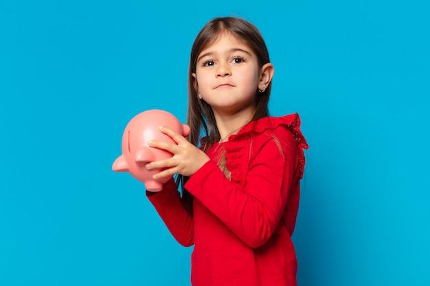 Całkiem mała dziewczynka smutny wyraz twarzy i trzymająca skarbonkę