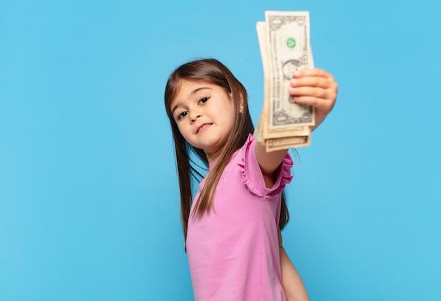 Całkiem mała dziewczynka szczęśliwa ekspresja i banknoty dolarowe