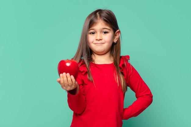 Całkiem mała dziewczynka szczęśliwa ekspresja i trzyma jabłko