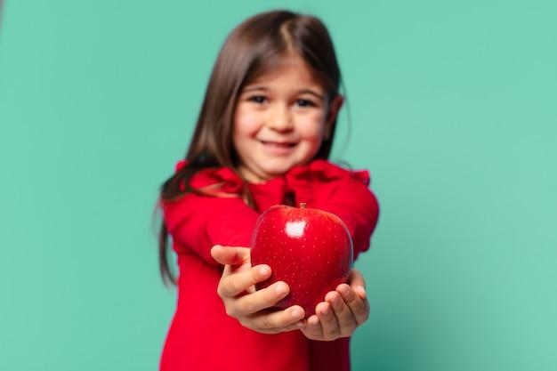 Całkiem mała dziewczynka szczęśliwa ekspresja i trzymająca jabłko