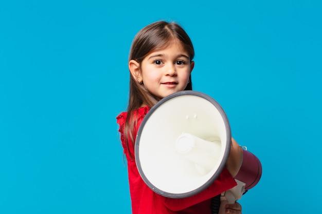 Całkiem mała dziewczynka szczęśliwa ekspresja i trzymająca megafon